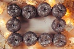 Обрамлять рождества серебряного украшения и светов яблок горя на бежевой деревянной предпосылке Стоковое Изображение