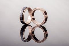 2 обручального кольца золота с диамантами и черным керамическим концом - вверх с отражением Стоковые Изображения RF