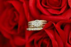 Обручальное кольцо группы диаманта установленное на красные розы Стоковые Фотографии RF