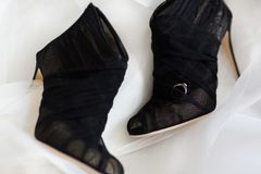 Обручальное кольцо на черных ботинках свадьбы на белой предпосылке стоковая фотография