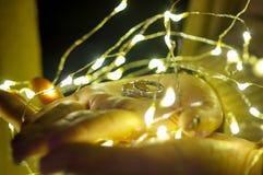 Обручальное кольцо счастливой руки и света приведенного вокруг части 2 Стоковые Изображения