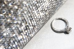 Обручальное кольцо с серебряной сумкой на белой таблице стоковые изображения