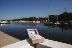 Обручальные кольца в деревянной коробке на предпосылке белых яхт в яхт-клубе стоковые фотографии rf