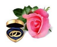 Обручальные кольца в золотистой коробке и подняли Стоковые Изображения