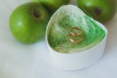 Обручальные кольца в кассете около зеленых яблок Стоковое Изображение