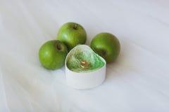 Обручальные кольца в кассете около зеленых яблок Стоковое фото RF