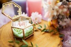 Обручальные кольца в шкатулке для драгоценностей на деревянной текстуре отделывают поверхность Стоковые Фото