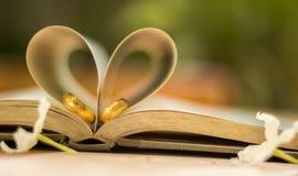 Обручальные кольца золота, книга сердца, нерезкость предпосылки Стоковое Изображение RF