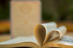 Обручальные кольца золота, книга сердца, нерезкость предпосылки Стоковое фото RF