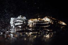 Обручальные кольца и серьги влажны, с падениями Отражения на стекле профессиональны стоковые изображения