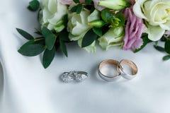 Обручальные кольца и серьги от белого золота с лежать драгоценных камней Стоковые Изображения