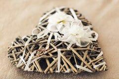 Обручальные кольца лежат на декоративном сердце лозы, украшенном с искусственными цветками стоковые изображения rf
