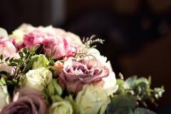 Обручальные кольца лежат на красивом букете свадьбы, обручальных кольцах Стоковая Фотография RF