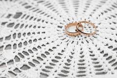 Обручальные кольца на белой предпосылке шнурка Стоковые Фото
