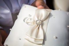 Обручальные кольца на белой holded подушке Стоковые Фото