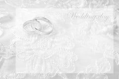 Обручальные кольца на карточке свадьбы, на белом платье свадьбы Стоковые Фотографии RF
