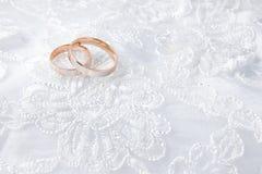 Обручальные кольца на карточке свадьбы, на белом платье свадьбы Стоковое Изображение RF