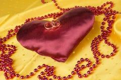 Обручальные кольца на красном сердце сатинировки на желтой предпосылке Стоковое Изображение RF