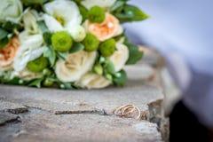 Обручальные кольца на предпосылке букета Стоковые Изображения RF