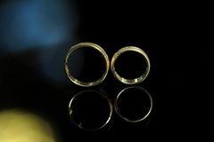 Обручальные кольца на черном стекле стоковые изображения rf