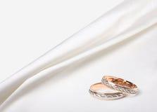 Обручальные кольца на silk предпосылке Стоковые Фото