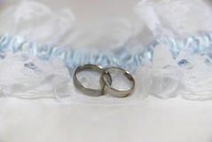 2 обручального кольца белых золота на белой пусковой площадке шнурка и голубой подвязке Стоковые Изображения RF