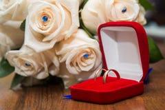 2 обручального кольца в красной коробке лежа на букете Стоковые Фото