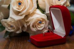 2 обручального кольца в красной коробке лежа на букете Стоковое фото RF