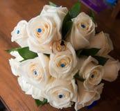 2 обручального кольца лежат на букете белых роз Стоковое фото RF