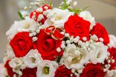 2 обручального кольца золота лежат на букете красного цвета и белых роз Стоковое фото RF