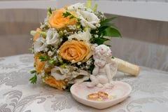 2 обручального кольца золота лежат на диске в форме розы с скульптурой ангела около bride& x27; букет s Стоковые Фото
