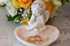 2 обручального кольца золота лежат на диске в форме розы с скульптурой ангела около букета оранжевых роз и whit Стоковые Изображения RF