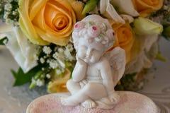 2 обручального кольца золота лежат на диске в форме розы с скульптурой ангела около букета Стоковые Изображения RF