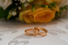 2 обручального кольца золота лежат на таблице около букета оранжевых роз и белых цветков Стоковая Фотография RF