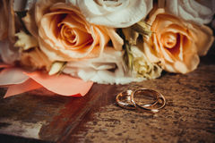 2 обручального кольца и букет апельсина и белых роз Стоковое Изображение