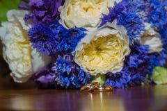 2 обручального кольца и букет голубых, белых и фиолетовых цветков Стоковая Фотография RF