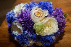 2 обручального кольца и букет голубых, белых и фиолетовых цветков Стоковое Фото
