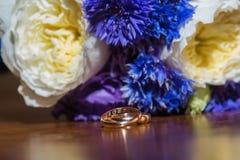 2 обручального кольца и букет голубых, белых и фиолетовых цветков Стоковые Изображения