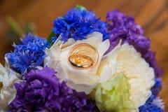 2 обручального кольца и букет голубых, белых и фиолетовых цветков Стоковые Фото