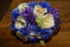 2 обручального кольца и букет голубых, белых и фиолетовых цветков Стоковое Изображение RF
