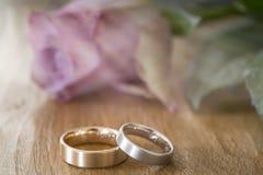 2 обручального кольца на деревянной поверхности с подняли Стоковое Фото