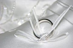 Обручальное кольцо белого золота на белой пусковой площадке шнурка Стоковые Фотографии RF