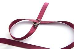 Обручальное кольцо в бургундской ленте изолированной на белой предпосылке стоковое изображение rf