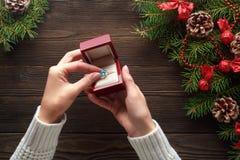 Обручальное кольцо в женских руках среди украшений рождества на деревянной предпосылке Стоковые Изображения RF