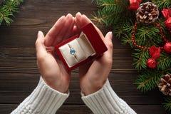 Обручальное кольцо в женских руках среди украшений рождества на деревянной предпосылке Стоковые Изображения