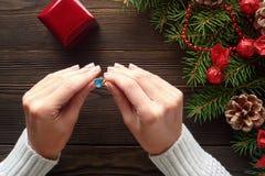Обручальное кольцо в женских руках среди украшений рождества на деревянной предпосылке Стоковые Фотографии RF