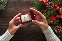 Обручальное кольцо в женских руках среди украшений рождества на деревянной предпосылке Стоковое Изображение RF