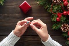 Обручальное кольцо в женских руках среди украшений рождества на деревянной предпосылке Стоковая Фотография RF