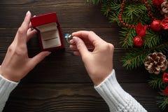 Обручальное кольцо в женских руках среди украшений рождества на деревянной предпосылке Стоковое фото RF