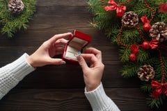 Обручальное кольцо в женских руках среди украшений рождества на деревянной предпосылке Стоковая Фотография